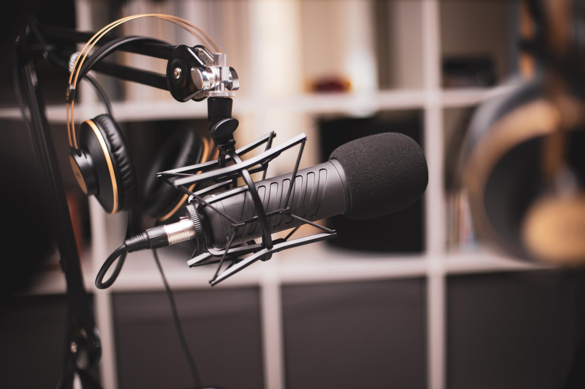 Side on a shot of a podcasting set-up with headphones and a professional microphone by Jonathan Farber