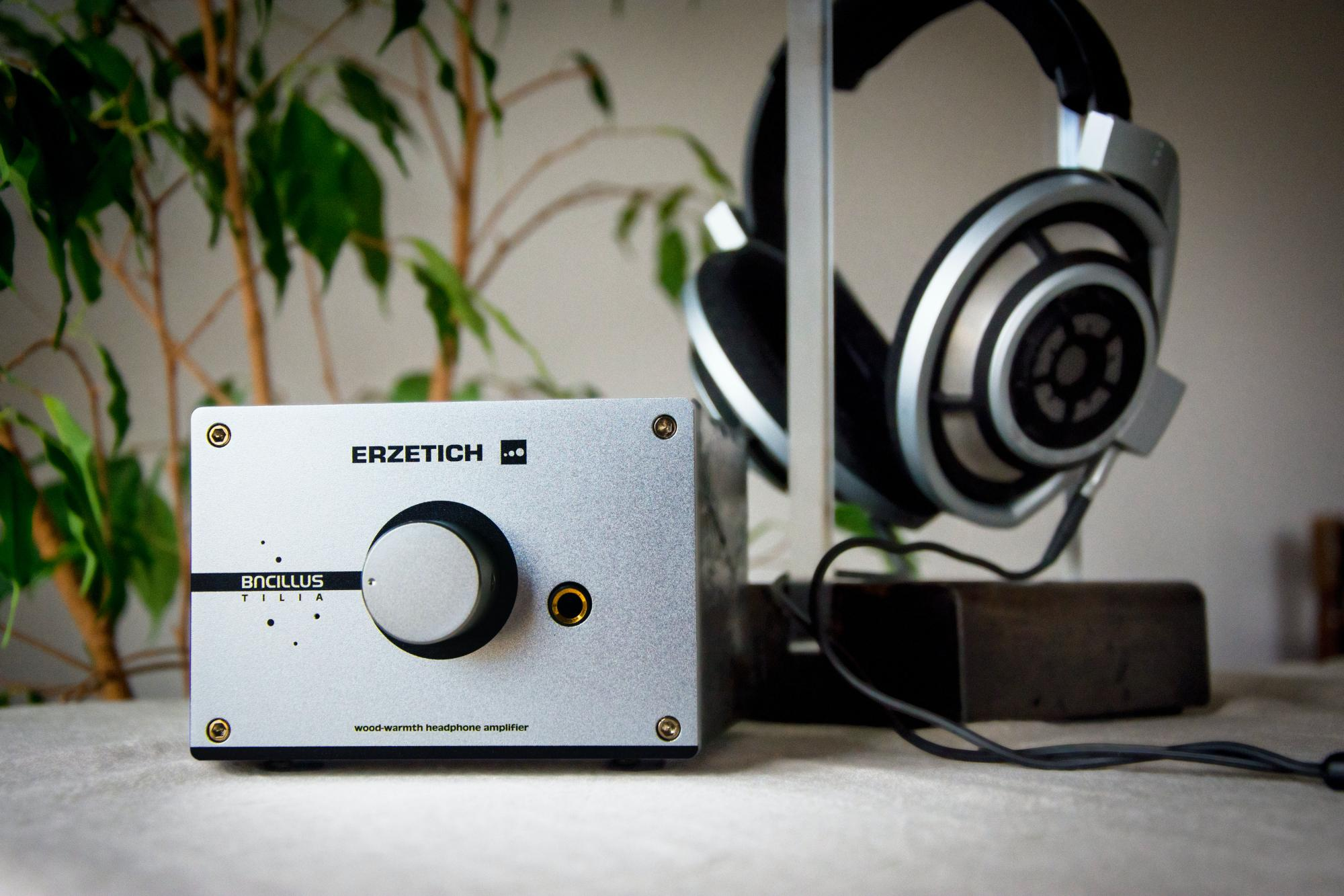 Headphone amplifier on a desk with headphones in the background by Blaz Erzetic