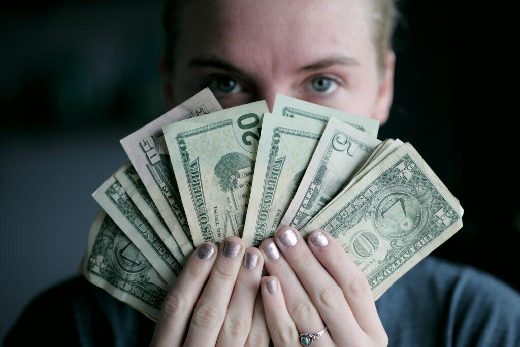 Person holding money greedily